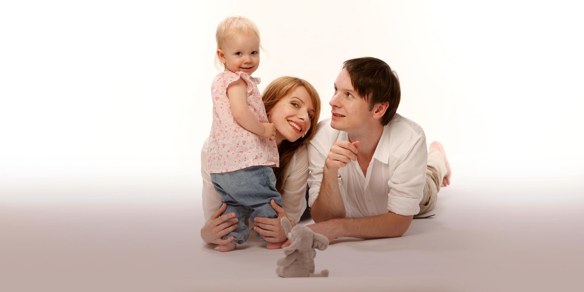 Familienfoto in hellen Farbtönen von einem neugierig schauenden Mann, einer lächelnden, rothaarigen Frau, die liegend ihre Arme auf dem Boden abstützt und ein stehendes, blondes Mädchen vor sich festhält.