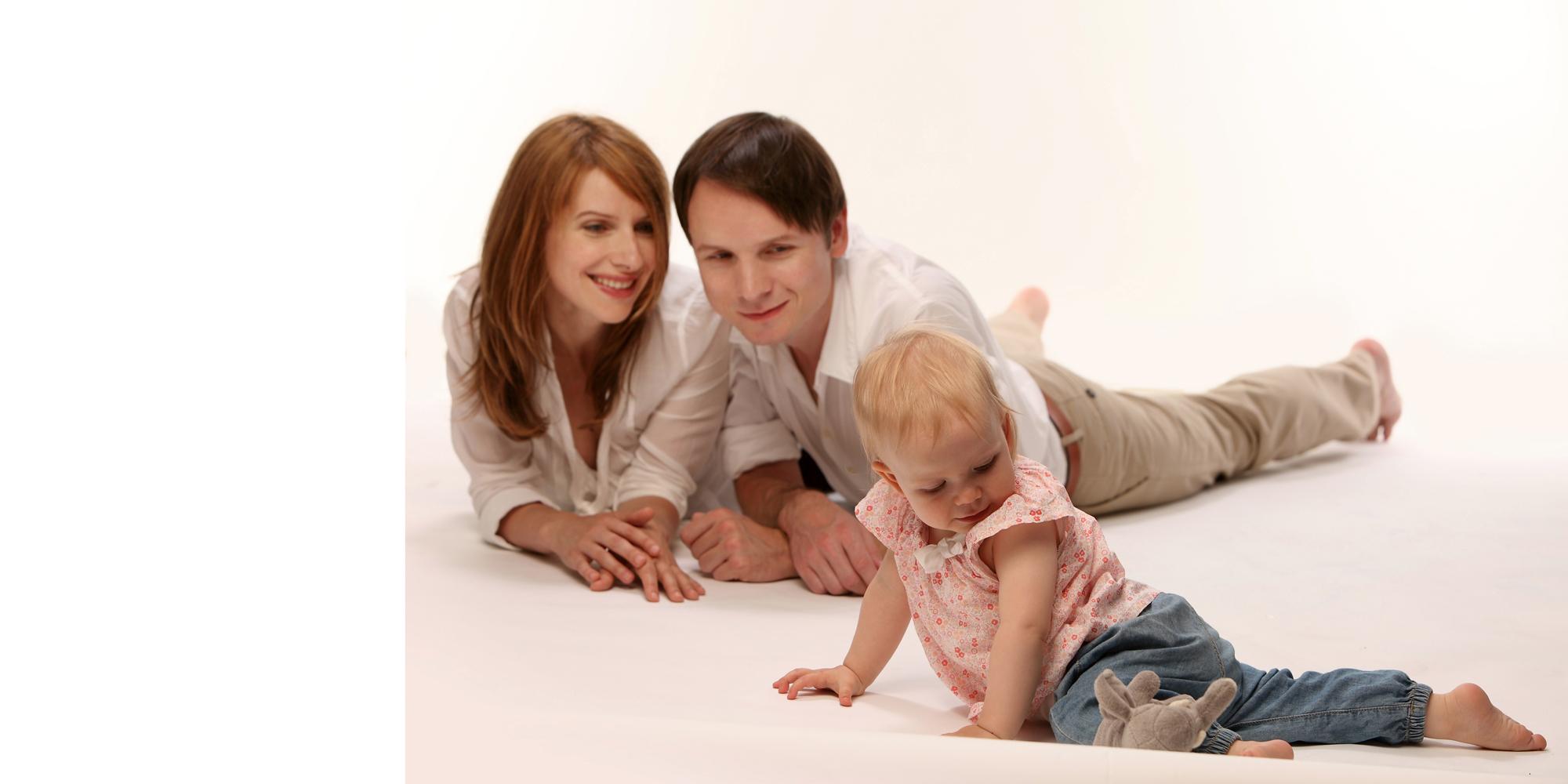 Familienfoto von einem Mann und einer rothaarigen Frau, die eng beieinander auf dem Boden liegen, ihre Arme vor sich abstützen und ein kleines, blondes Mädchen beobachten, das vor ihnen auf dem Boden sitzt und mit einem grauen Teddy spielt.