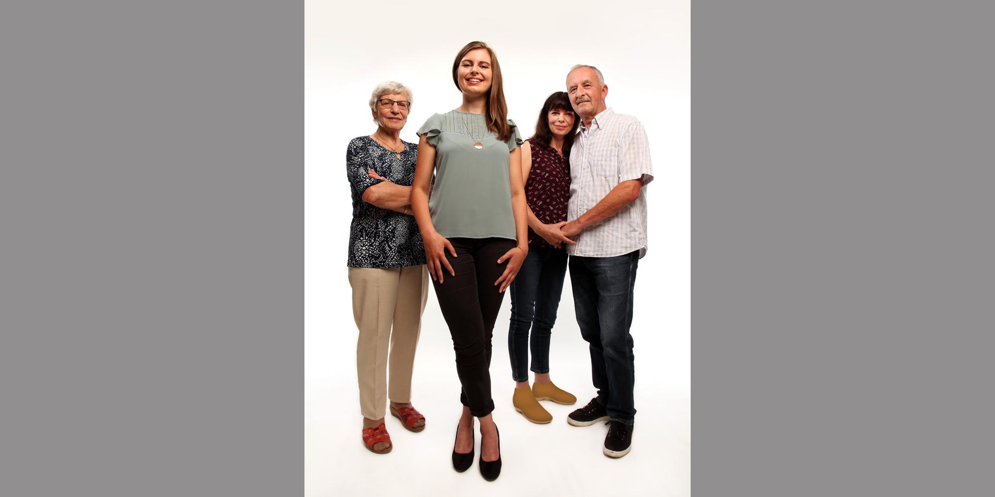 Ganzkörperportrait von einem älteren Mann, der eine Frau im Arm hält, einer älteren Frau, die ihre Arme vor der Brust verschränkt und einer jungen, selbstbewusst lächelnden Frau, die mit überkreuzten Beinen im Vordergrund für Familienfoto posiert.