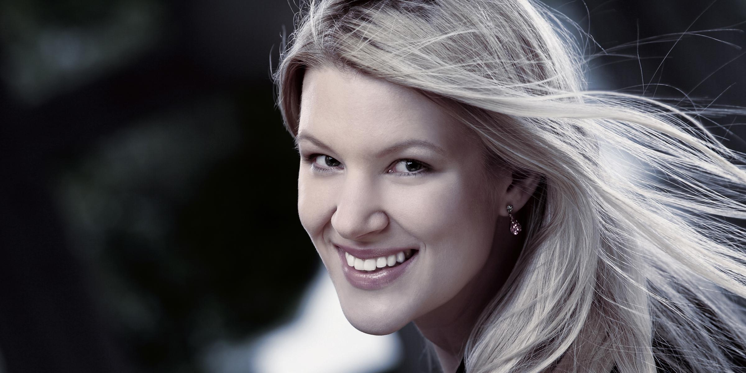 Portrait einer lächelnden Frau mit fliegenden Haaren posiert für Business-Foto.
