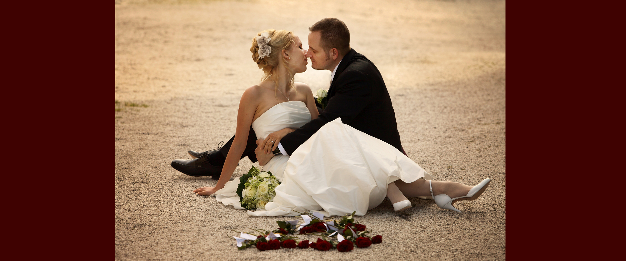 Hochzeitsportrait eines Mannes im dunklen Anzug und einer blonden Frau im weißen Brautkleid (Brautpaar), die umschlungen auf dem Boden sitzen und sich küssen.