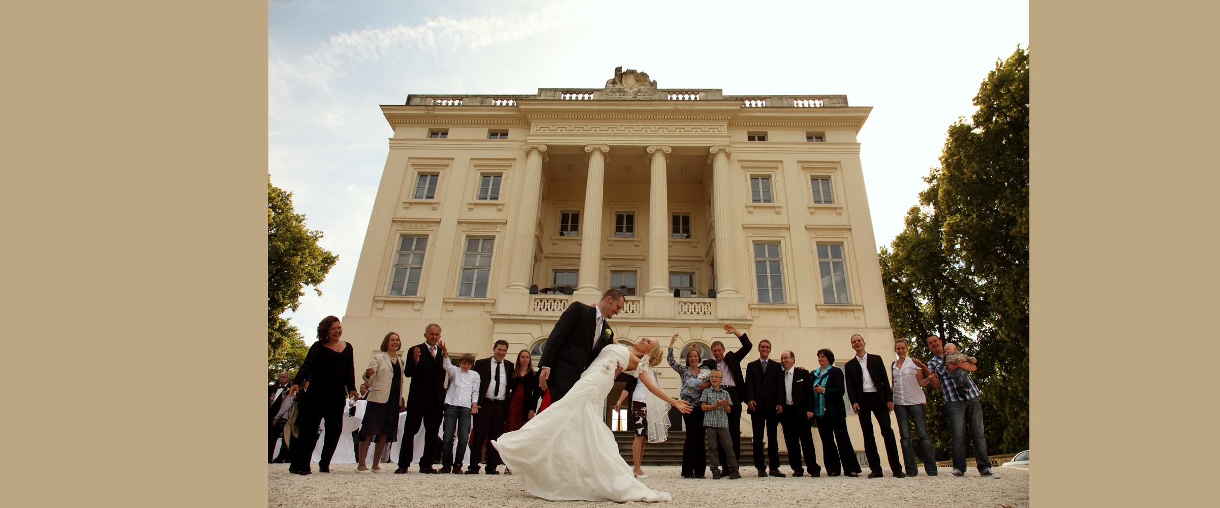 Hochzeitsportrait eines Mannes im dunklen Anzug, der eine Frau im weißen Brautkleid seitlich im Arm hält (Brautpaar), während im Hintergrund eine größere Menschenmenge freundlich winkt und vor einem hohen Gebäude Schloss Monaise Trier) posiert.
