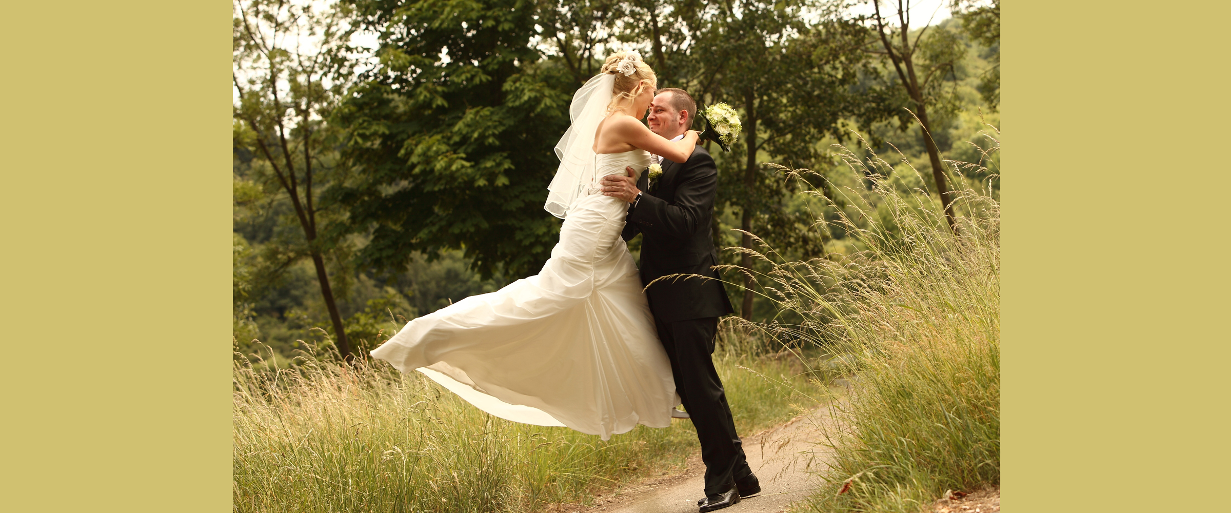 Hochzeitsportrait in der Natur eines lächelnden Mannes im dunklen Anzug, der eine blonde Frau hoch hebt, die ein weißes Brautkleid mit Schleppe trägt (Brautpaar).