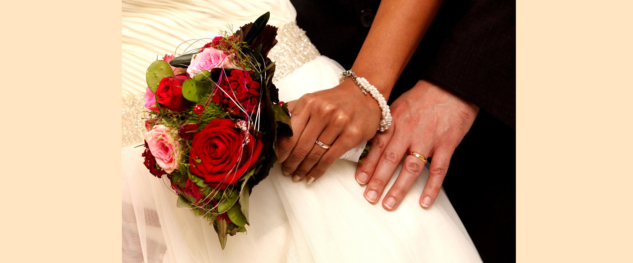 Hochzeitsportrait von der Hand eines Mannes und einer Frau (Brautpaar) mit goldenen Eheringen, und die Frau hält einen Brautstrauß aus Rosen fest.