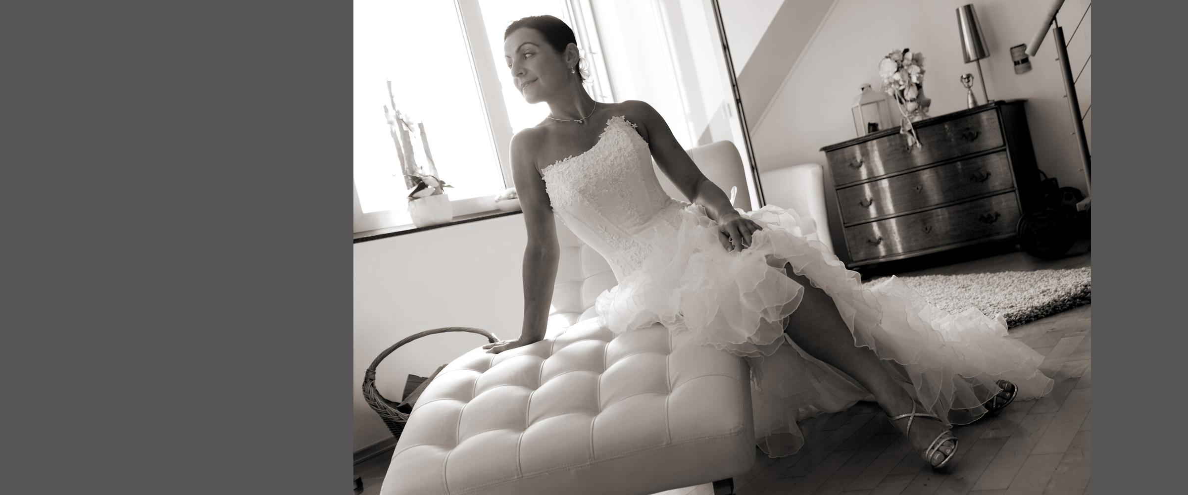 Schwarz-weißes Hochzeitsportrait einer Frau im weißen Brautkleid, die seitlich auf einer Liege sitzend, posiert.