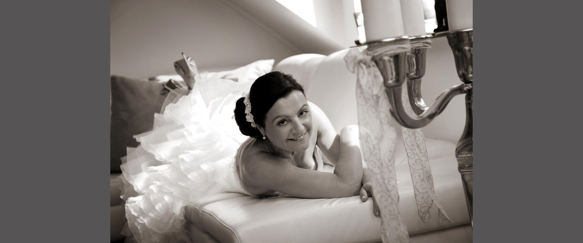 Schwarz-weißes Hochzeitsportrait einer dunkelhaarigen Frau im weißen Brautkleid, die freundlich lächelnd und auf einem weißen Sofa liegend, posiert.
