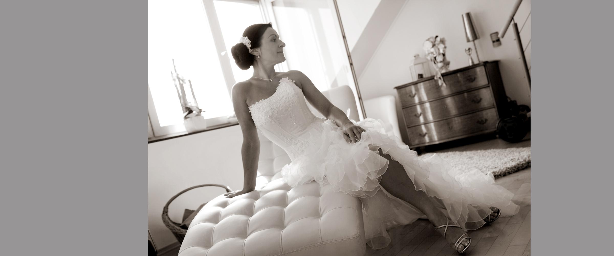 Schwarz-weißes Hochzeitsportrait einer Frau im weißen Brautkleid, die seitlich auf einer weißen Liege sitzt und zur Seite blickend posiert.