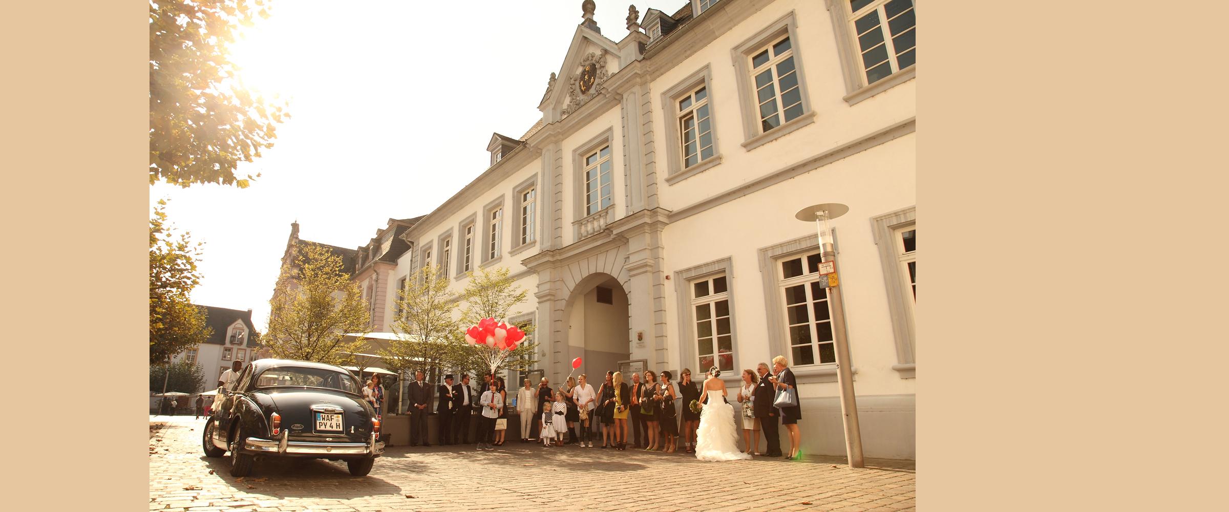 Hochzeitsportrait einer Menschenmenge mit Luftballons (Hochzeitsgesellschaft) vor einem hohen Gebäude (Standesamt Trier, Turm Jerusalem), und die Braut, im weißen Kleid, posiert für Hochzeitsfotografie in Rückenansicht mittendrin.