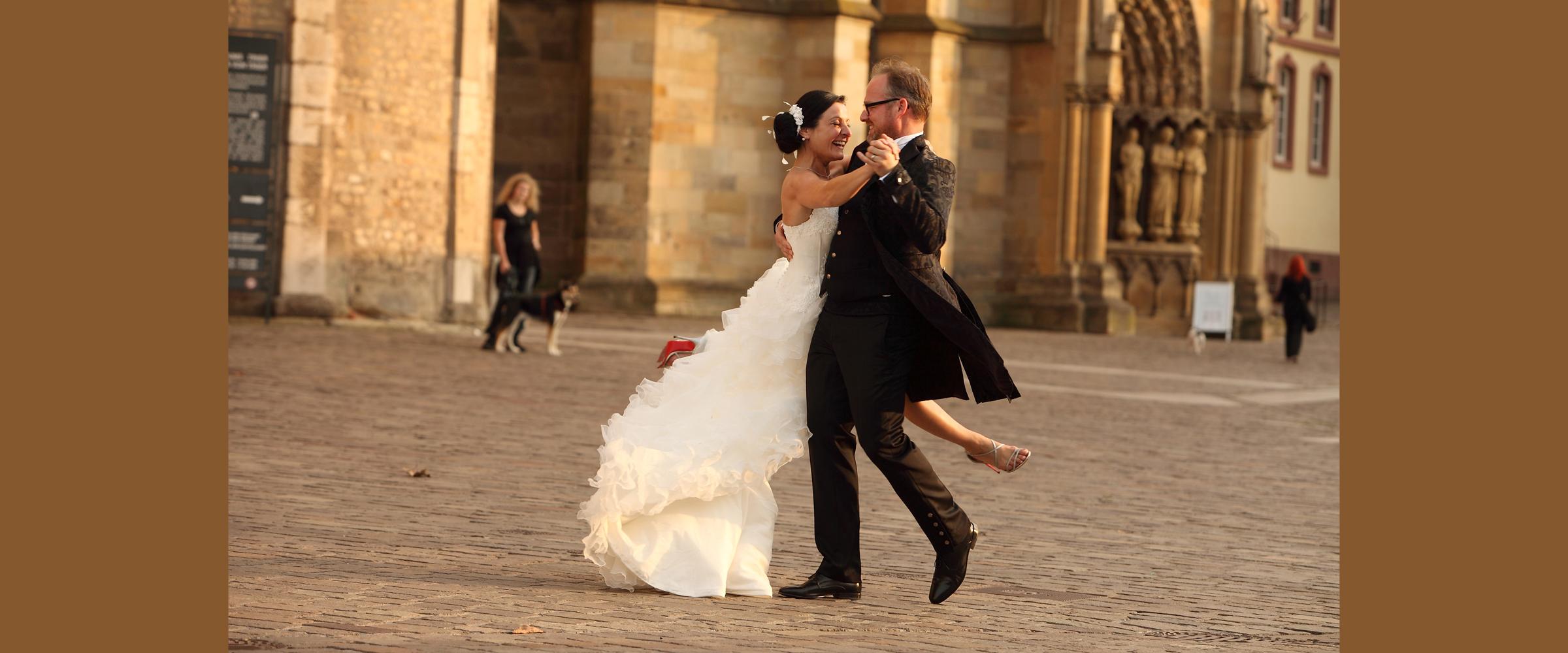 Hochzeitsportrait eines Mannes im schwarzen Frack und einer dunkelhaarigen Frau im weißen Brautkleid, die lächelnd vor dem Hintergrund eines Gebäudes (Dom Trier) tanzen.