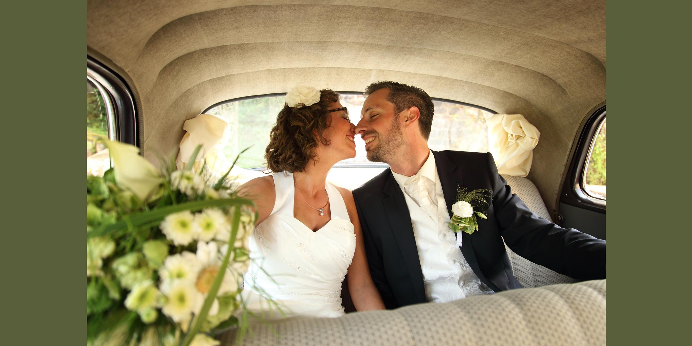 Hochzeitsportrait eines Mannes im dunklen Anzug und einer Frau im weißen Brautkleid (Brautpaar), die lächelnd auf dem Rücksitz eines, mit Blumen geschmückten, Autos sitzen und sich küssen wollen.