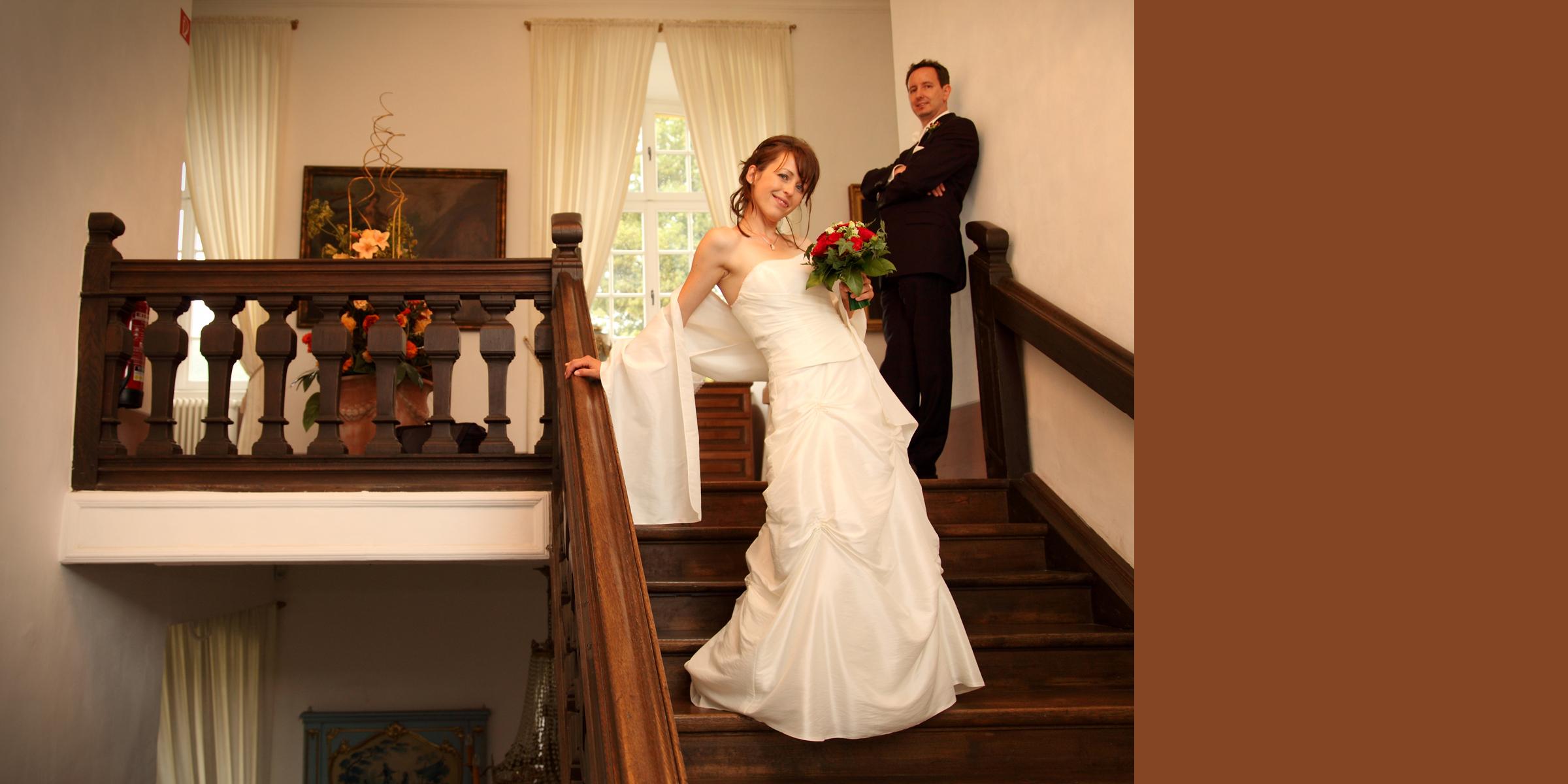 Hochzeitsportrait eines Mannes im dunklen Anzug mit roter Krawatte, der eine Frau in weißem Brautkleid, mit Brautstrauß, auf Händen trägt und beide posieren lächelnd vor dem Hintergrund eines Gebäudes (Palastgarten Trier).