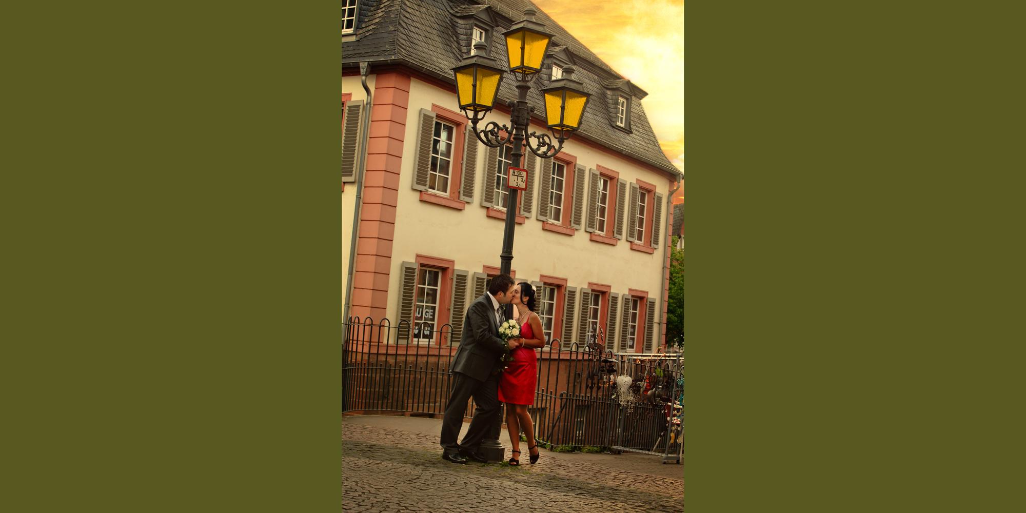 Hochzeitsportrait eines Mannes im dunklen Anzug und einer Frau im roten Kleid (Brautpaar), die sich vor dem Hintergrund einer Laterne und eines Altbaus küssen und einen weißen Brautstrauß zwischen sich festhalten.(Wasserfall Saarburg).
