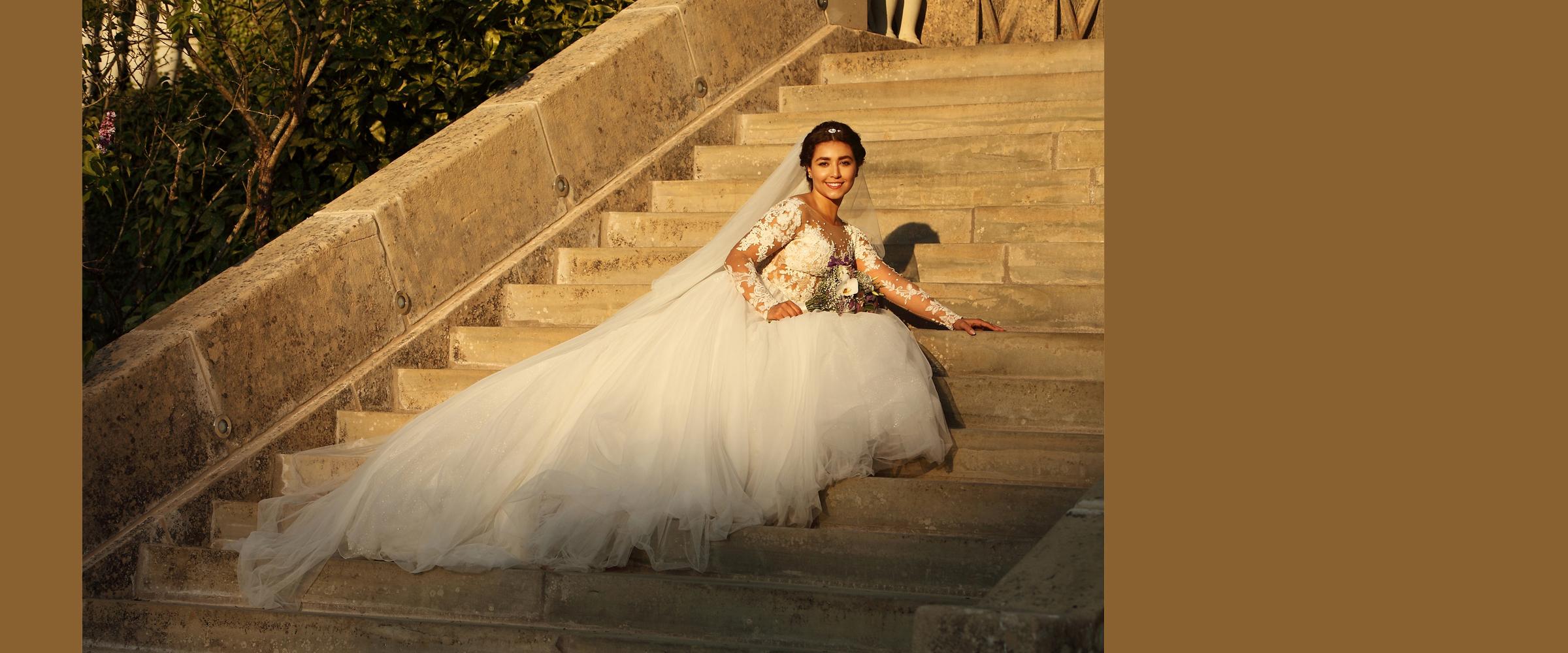 Hochzeitsportrait einer strahlenden Frau mit hochgesteckten Haaren, die in einem weißen Brautkleid mit langer Schleppe auf den Stufen einer hoch zulaufenden Steintreppe sitzt.