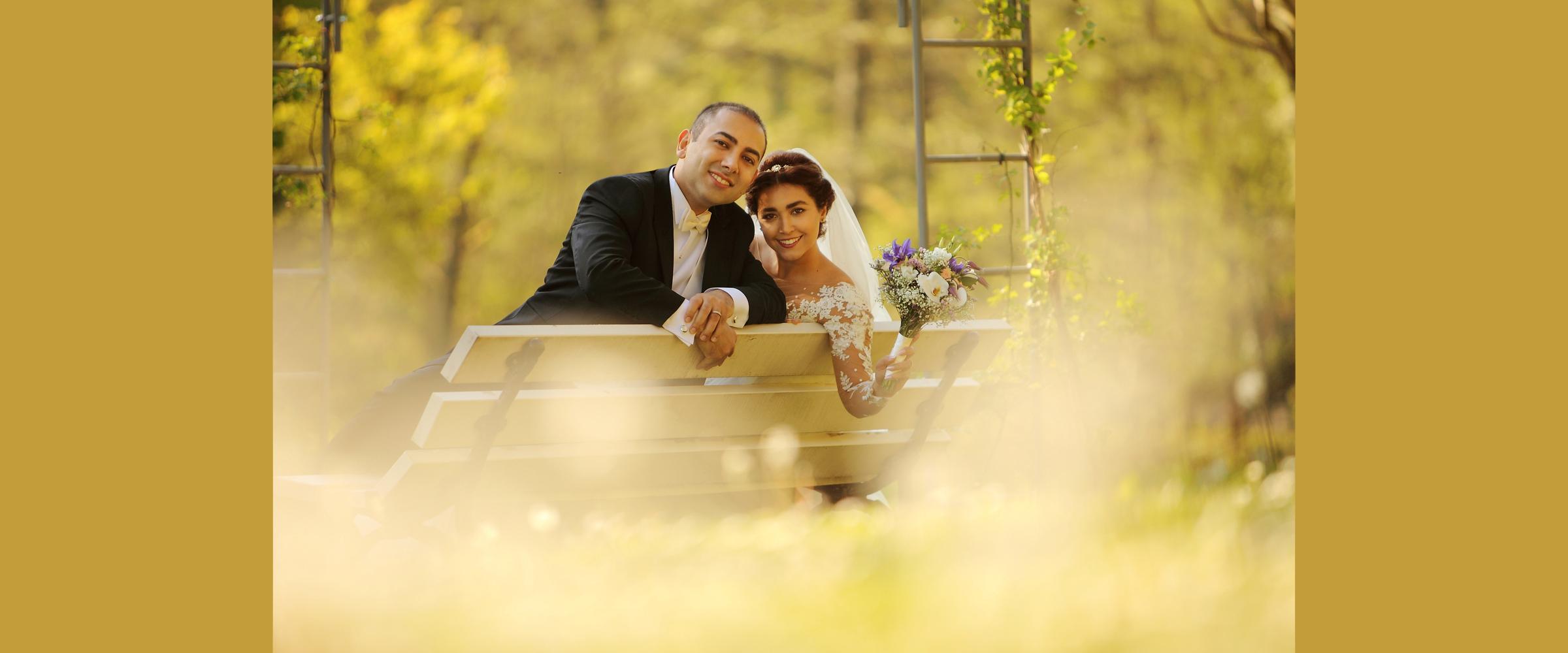 Hochzeitsportrait eines Mannes im dunklen Anzug und einer Frau im Brautkleid, die einen Brautstrauß in der Hand hält (Brautpaar), die lächelnd und rückwärts auf einer weißen Parkbank in der Natur sitzen.