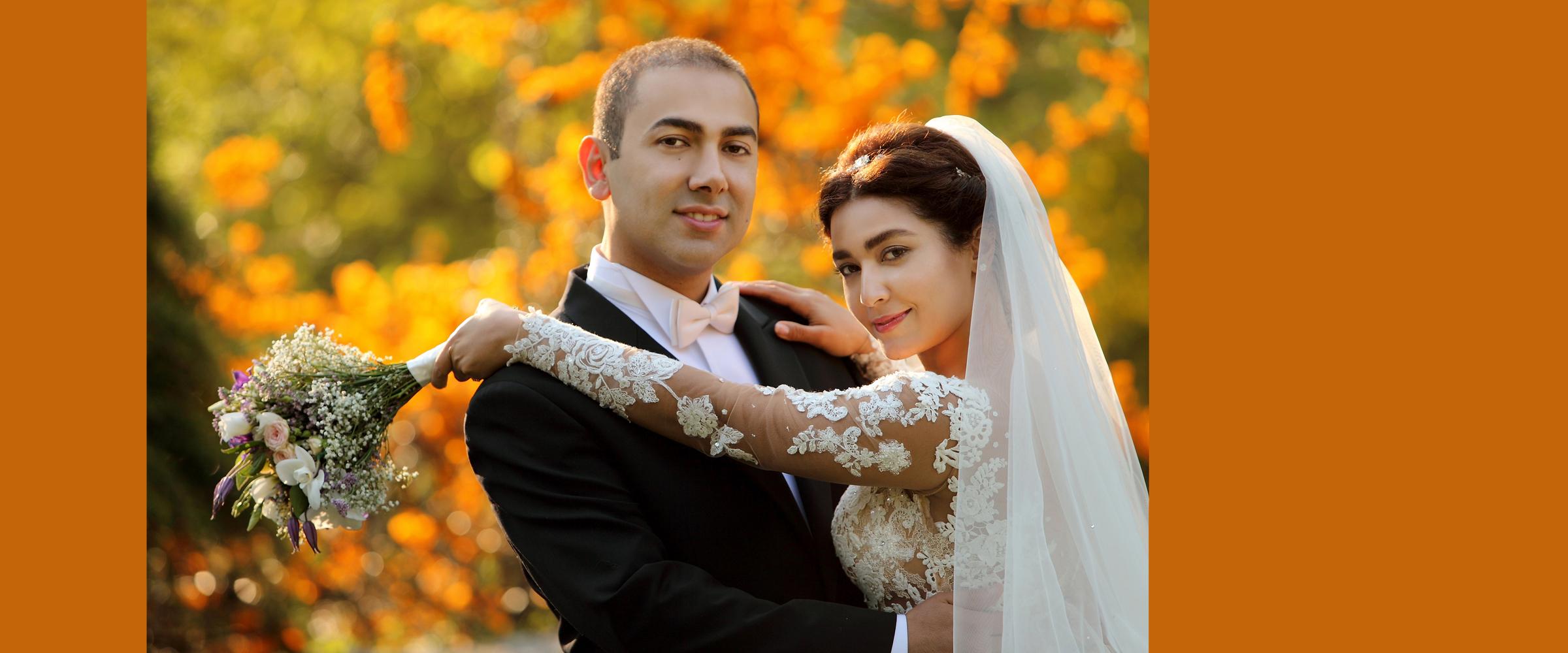 Hochzeitsportrait eines Mannes im dunklen Anzug, der eine Frau im Arm hält, die ein weißes, blumenbesticktes Brautkleid mit langer Schleppe trägt und einen Brautstrauß in der Hand hält (Brautpaar).