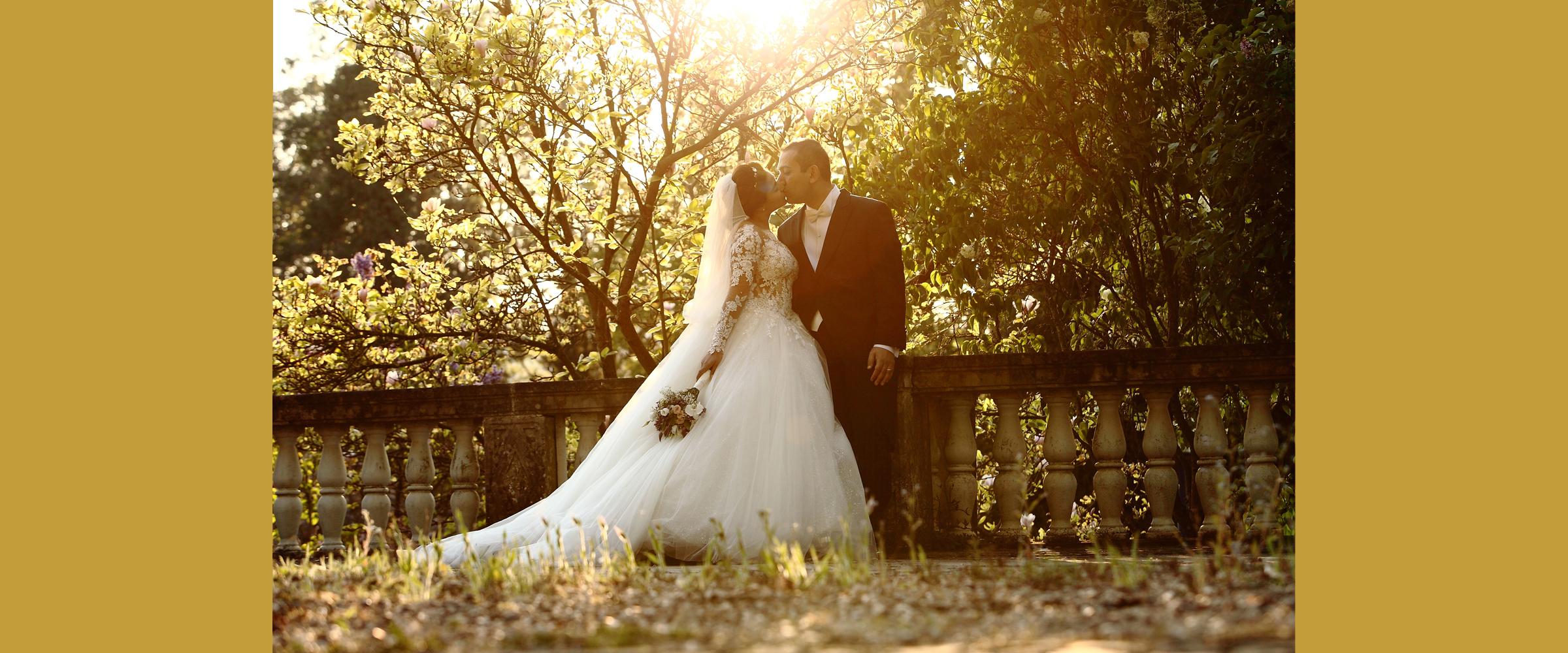 Hochzeitsportrait eines Mannes im dunklen Anzug und einer Frau im weißen Brautkleid mit langer Schleppe (Brautpaar), die eng beieinander stehen und sich, vor einem Geländer stehend, küssen.