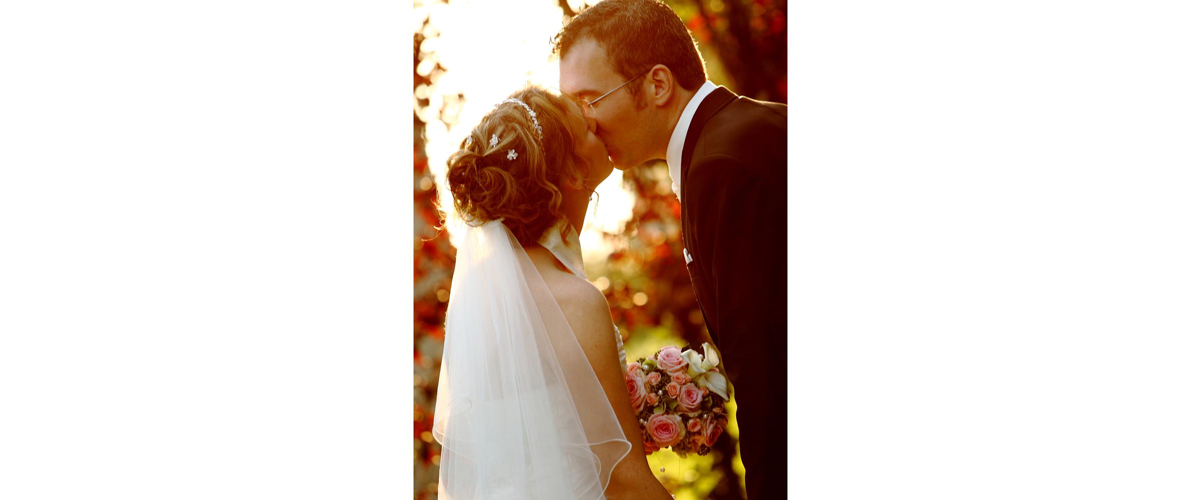 Hochzeitsportrait eines Mannes im dunklen Anzug, der eine Frau im weißen Brautkleid mit Schleier küsst (Brautpaar).