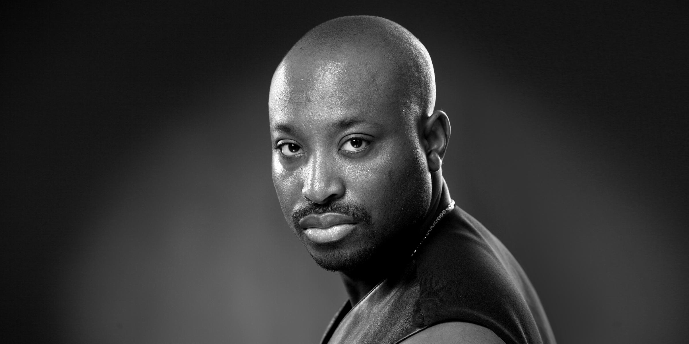 Seitliches Frontportrait in schwarz-weiß eines exotischen Mannes mit ernstem Blick posiert für Bewerbungsfoto und Portrait.