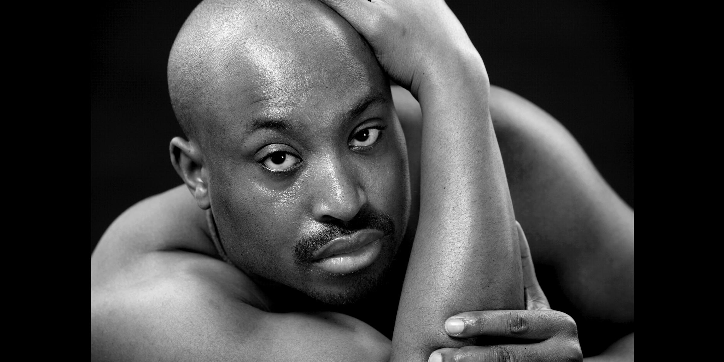 Ein Mann mit nacktem muskulösem Oberkörper und ernstem Blick posiert für schwarz-weiß Portrait.