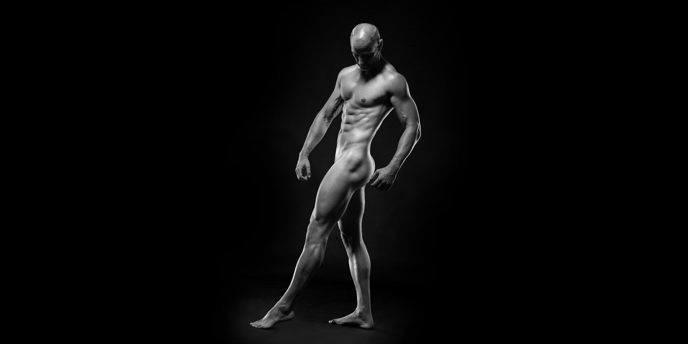 Seitenansicht eines muskulösen, sportlichen Mannes mit versetzter Beinstellung und gesenktem Blick in schwarz-weiß.