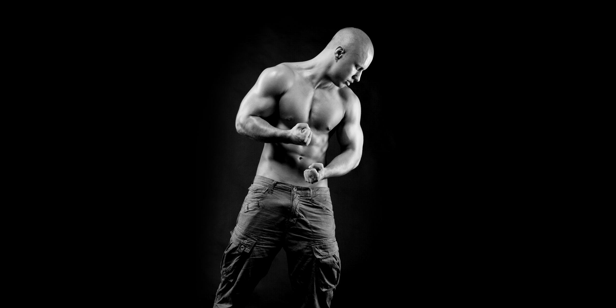 Schwarz-weiße Frontansicht eines muskulösen Mannes, der in Jeans und mit freiem Oberkörper posiert und die Fäuste ballt.