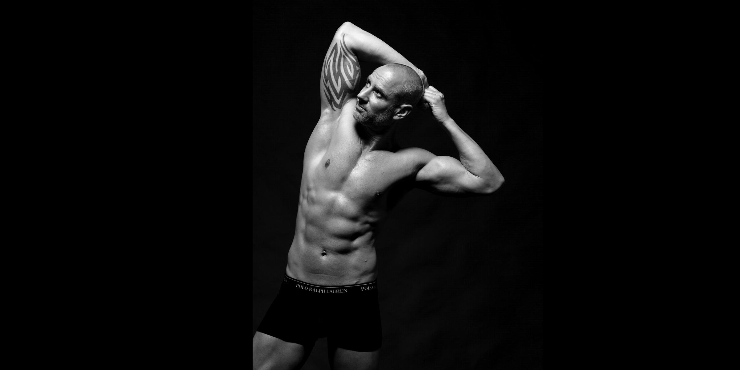 Schwarz-weiß Oberkörper-Portrait eines muskulösen Mannes mit auffälligen Oberarm-Tattoo, der mit angespannten Armen über dem Kopf posiert.