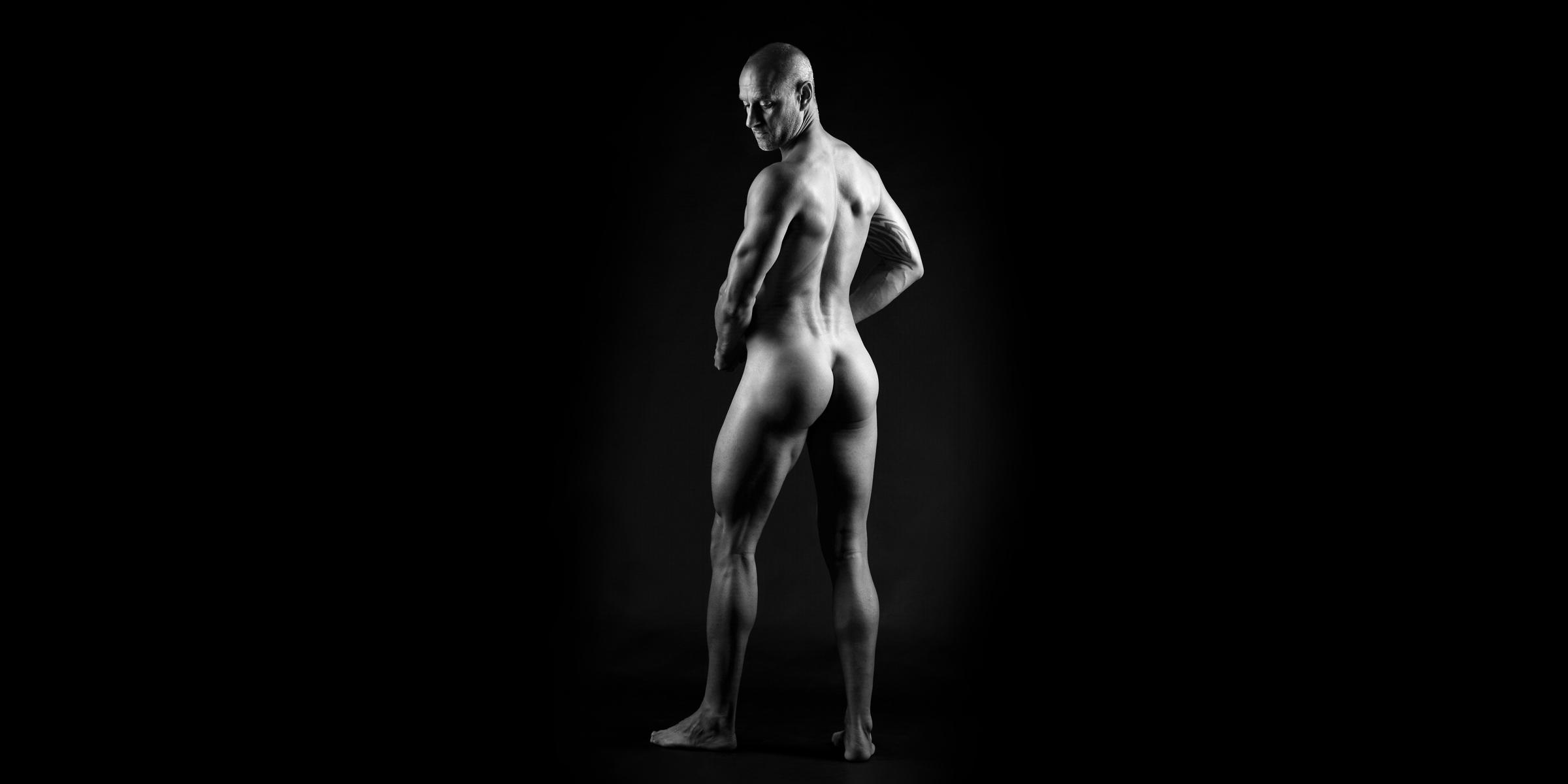 Schwarz-weiße Rückansicht eines nackten, sportlichen Mannes, der seitlich nach unten blickt.