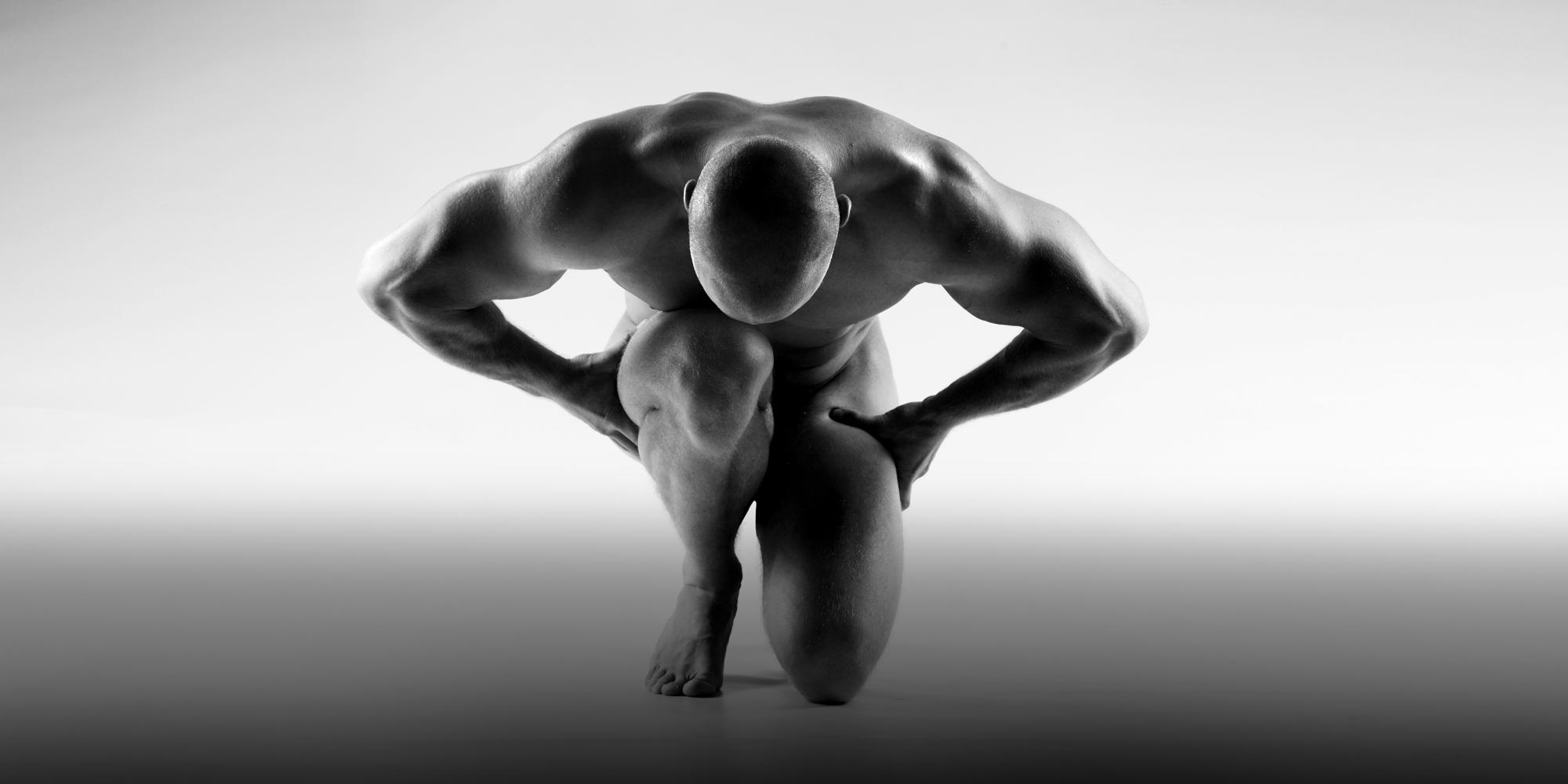 Schwarz-weißes Portrait eines knienden, nackten Mannes, der die Hände auf den Oberschenkeln abstützt und den Kopf auf sein Knie ablegt.