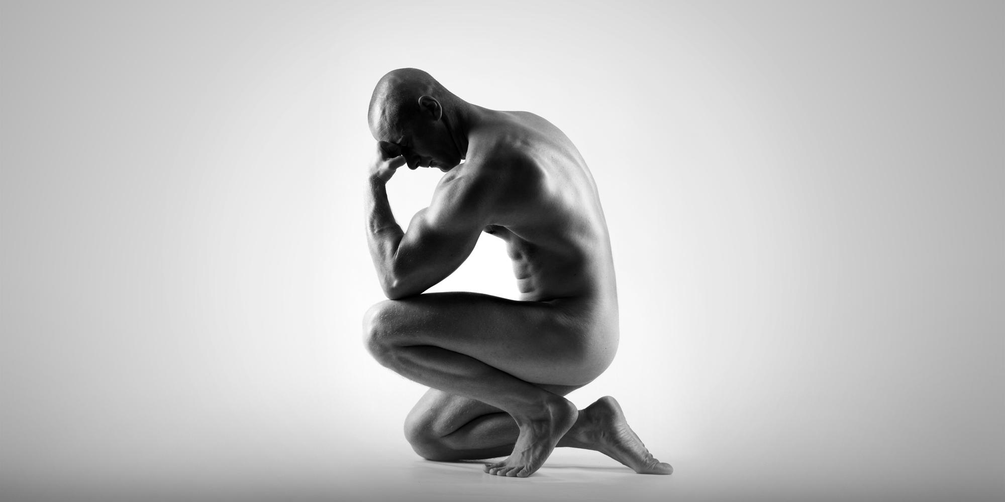 Seitliches Portrait eines knienden, nackten Mannes, der seine Stirn auf der Faust seines angewinkelten Armes ablegt.