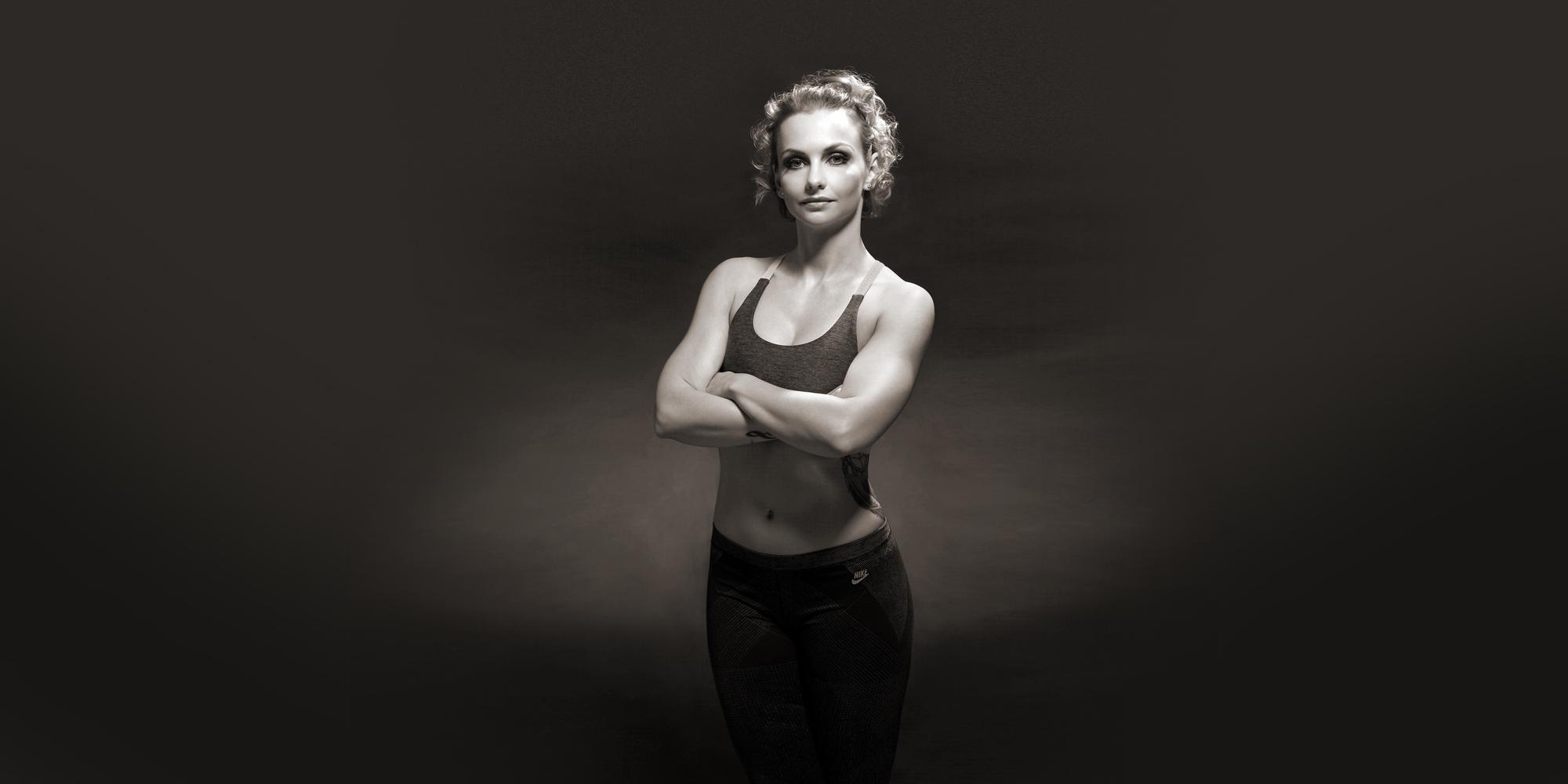 Frontportrait in schwarz-weiß einer Frau in sportlichem Outfit und mit neutralem Gesichtsausdruck, die ihre Arme vor der Brust gekreuzt hat.
