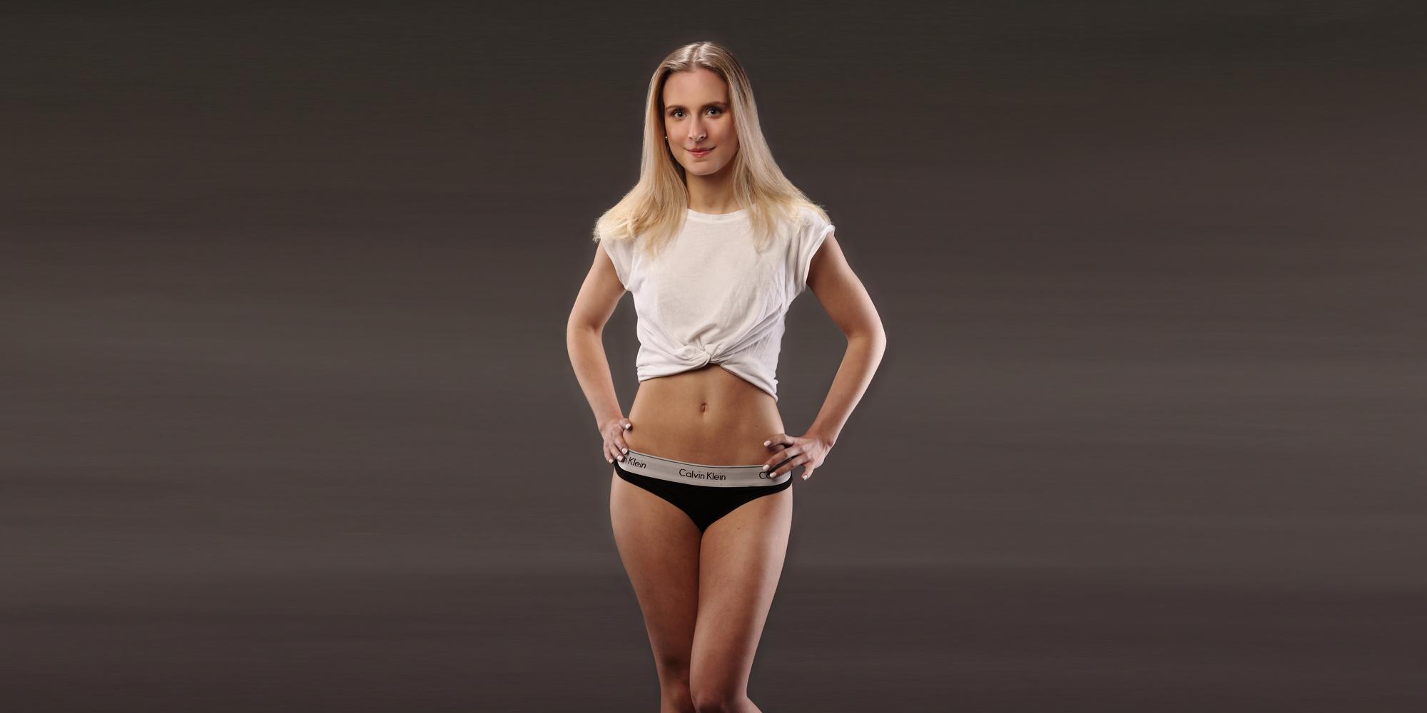 Frontportrait in Farbe eines jungen, blonden Frau in sportlicher Unterwäsche und Top, die selbstbewusst ihre Hände auf der Hüfte ablegt.