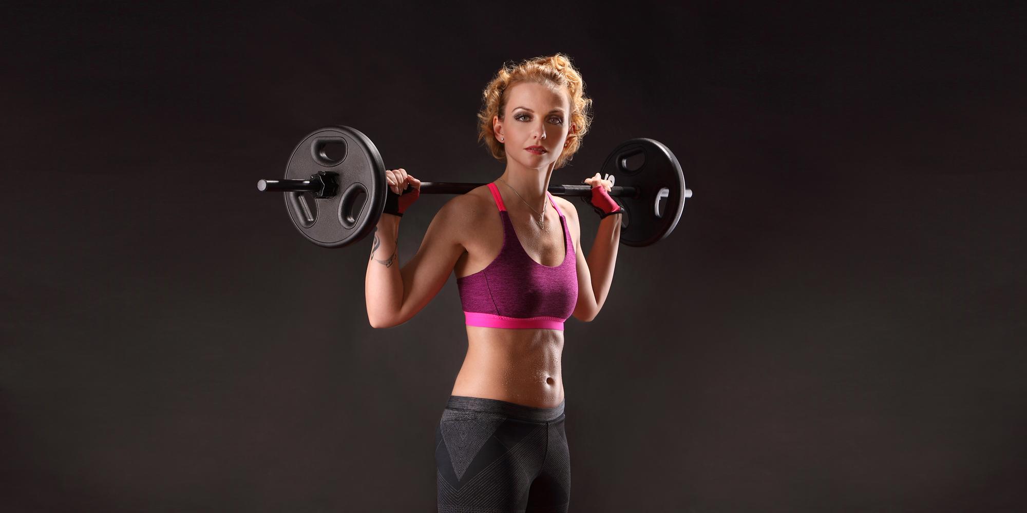 Seitliches Frontportrait in Farbe einer Frau in sportlichem Outfit, die eine Hantelstange auf ihrer Schulter abgelegt hat.