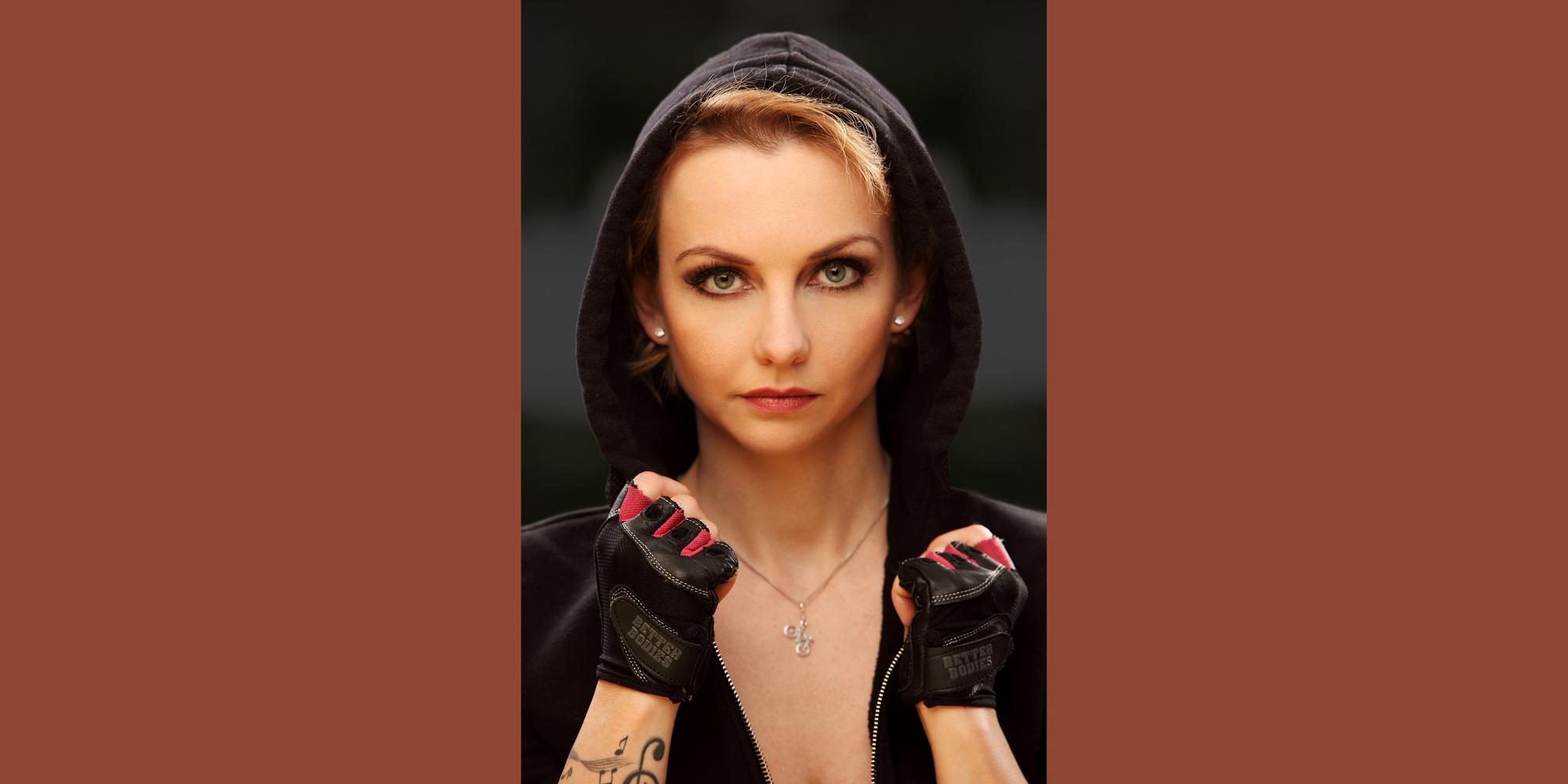 Frontportrait in Farbe von Gesicht und Dekolleté einer Frau, die eine sportliche Kapuze mit Handschuhen trägt und mit festem Blick in die Kamera schaut.