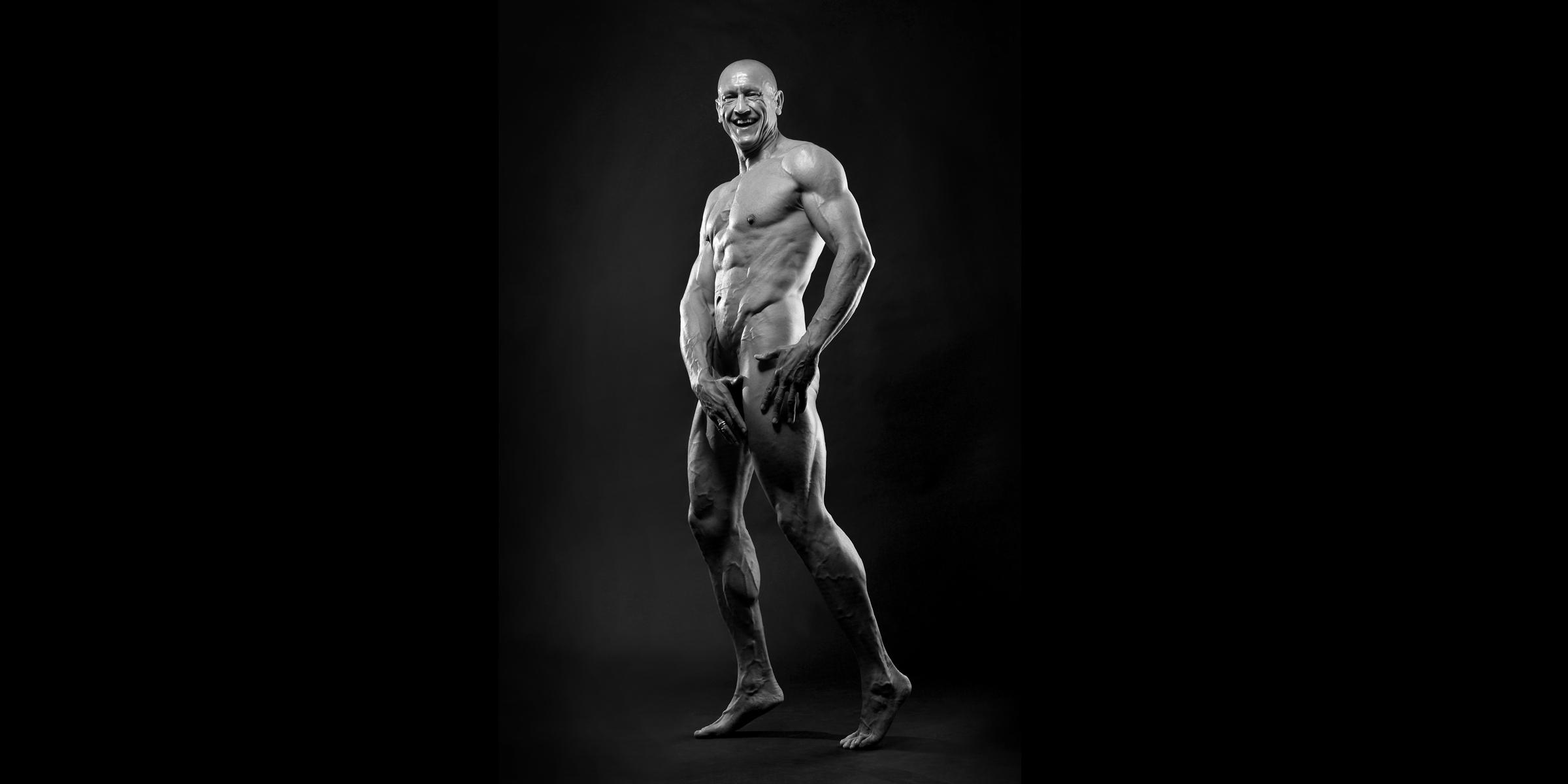 Schwarz-weiße Vorderansicht eines sportlichen Mannes, der freundlich lacht und seine Hände vor die Genitalien hält.