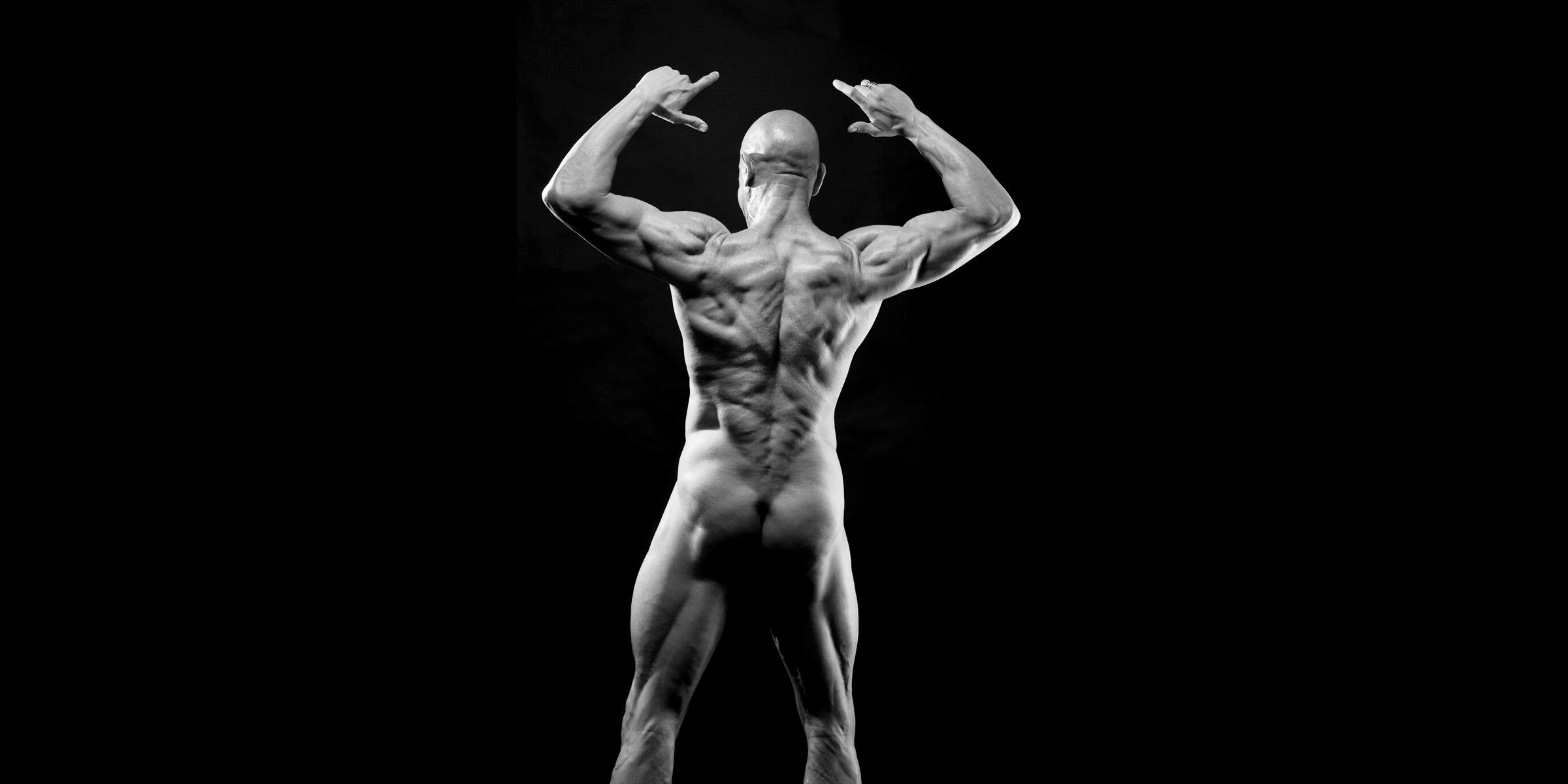 Rückansicht eines nackten, sportlichen Mannes mit besonders ausgeprägter Rückenmuskulatur, der mit gehobenen Armen und gespreizten Fingern posiert.