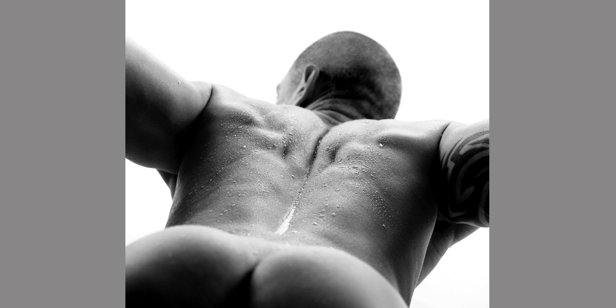 Bildausschnitt von Gesäß, Rücken und Hinterkopf eines liegenden sportlichen Mannes mit geperlten Wassertropfen auf der Haut.