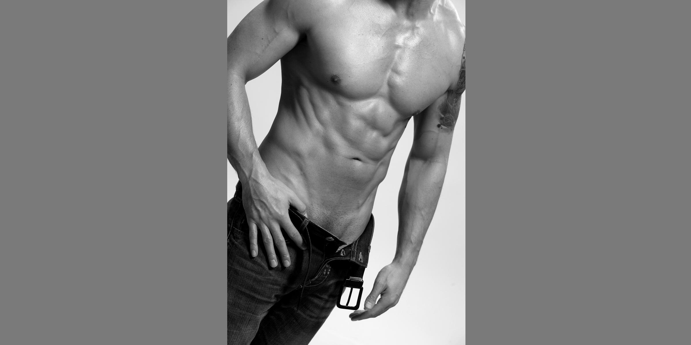 Schwarz-weißer Bildausschnitt von Brust und Bauch eines sportlichen Mannes in Jeans, die am oberen Knopf geöffnet ist.