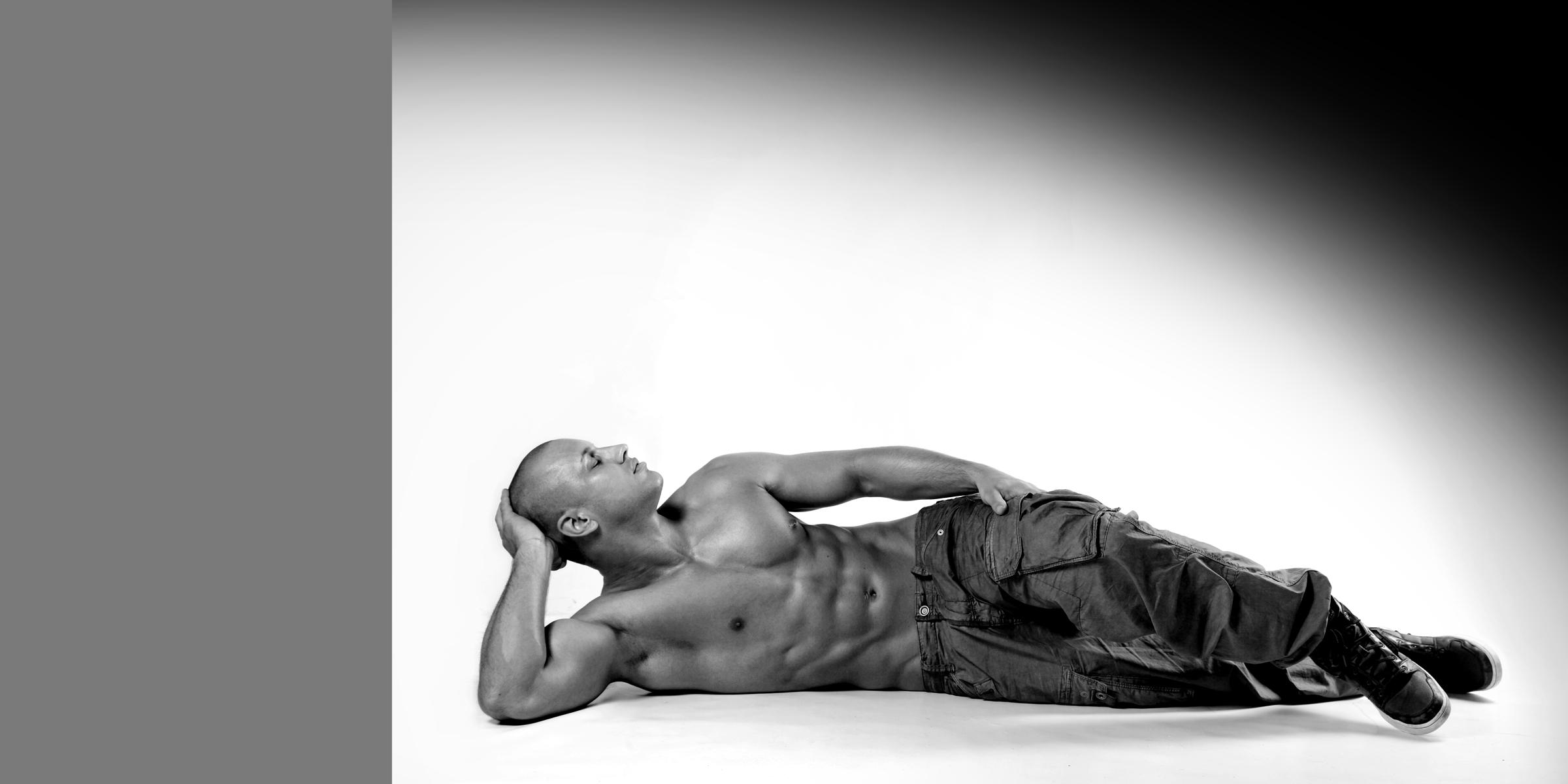 Ein sportlicher liegender Mann in Jeans, mit nacktem Oberkörper der die Augen entspannt geschlossen hat.