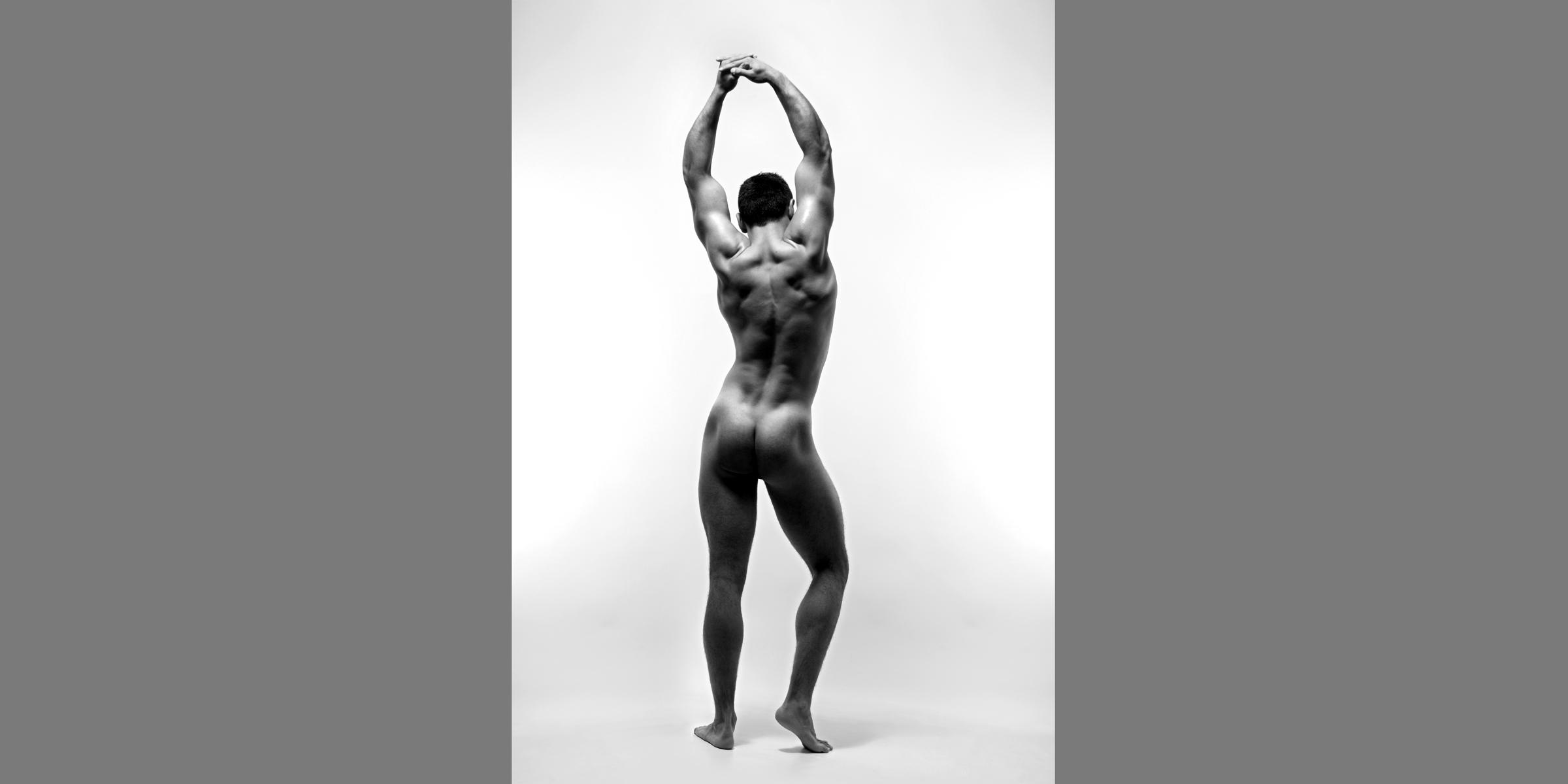 Schwarz-weiße Rückansicht eines sportlichen Mannes mit muskulösem Rücken, der die Arme über dem Kopf hochstreckt.